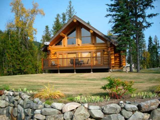 A-frame style log home with deck overlooking sprawling lawn.
