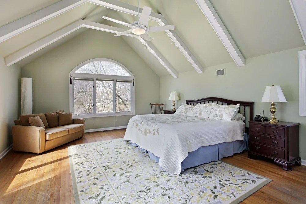 Traditional bedroom featuring a vaulted ceiling with beams along with a hardwood flooring topped by a classy rug.