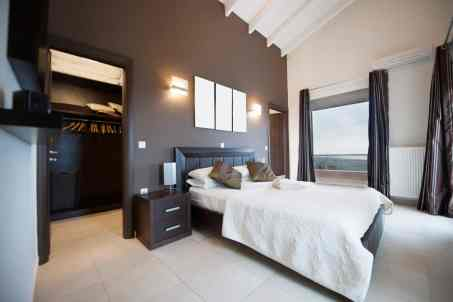 Modern master bedroom with a walk-in closet, dark accent wall, tile flooring and cathedral ceiling
