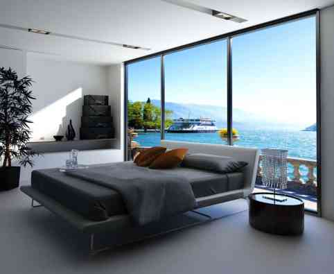 Black and white modern master bedroom with platform bed in an apartment with floor to ceiling window.
