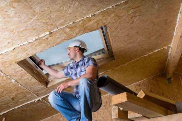 Bir erkek inşaat işçisi, tavan penceresinin çerçevesini incelemek için tavana yakın yükseltilmiş iskelede çömeliyor.  Parçacık kontrplak levha da açığa çıkar.