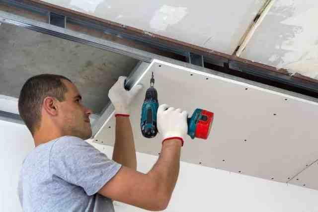 Bir inşaat işçisi, alçıpan ile asma tavanı monte ediyor.  Ayrıca alçıpanı tornavidayla tavan metal çerçevesine sabitliyor.