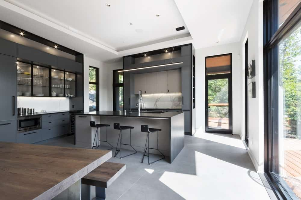 Black is often frowned upon in kitchen remakes because it makes the place look gloomy. But this kitchen goes all black nonetheless because the wall-length windows facing the kitchen accentuate the shade even more. No further lights are needed because sunlight does it all. Pristine and transparent glass cabinets are the best way to let all that china shine.