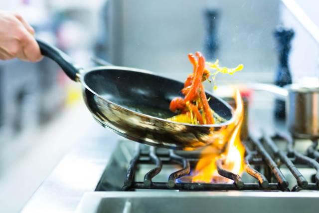 Şef yemek üzerinde flambe yapıyor.