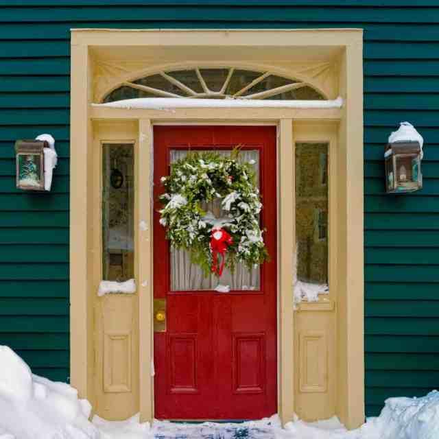 Yeşil bir dış cephe kaplaması, duvar aplikleri ve bir Noel çelengi ile süslenmiş ve kısmen karla kaplı kırmızı bir ön kapısı olan ev.
