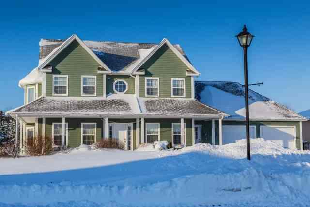 Bir kar fırtınasından sonra yeşil dış cephe kaplaması ile Kuzey Amerika müstakil ev.