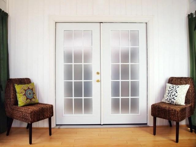 Sandalyelerle çevrili bir dizi buzlu cam Fransız kapı.