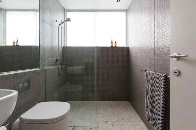 Bu, duvarlarda tam mozaik karolar ve zeminde mozaik karolar bulunan modern bir banyodur.