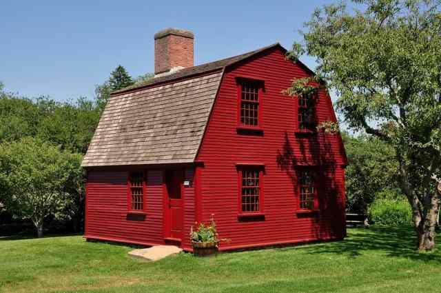 Koyu kırmızı dış duvarları, tuğla bacası ve gambrel çatısı olan kır evi tarzı bir ev.