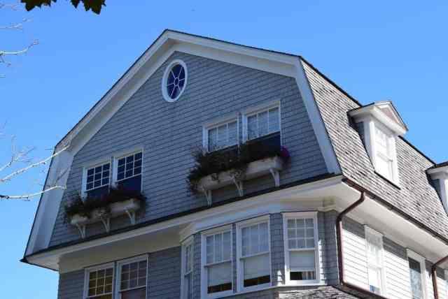Çatı pencereleri ve gambrel çatısı olan geleneksel tarzda bir eve yakından bakış.