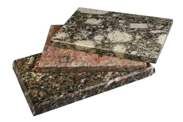 Beyaz bir yüzey üzerinde granit fayans parçaları.