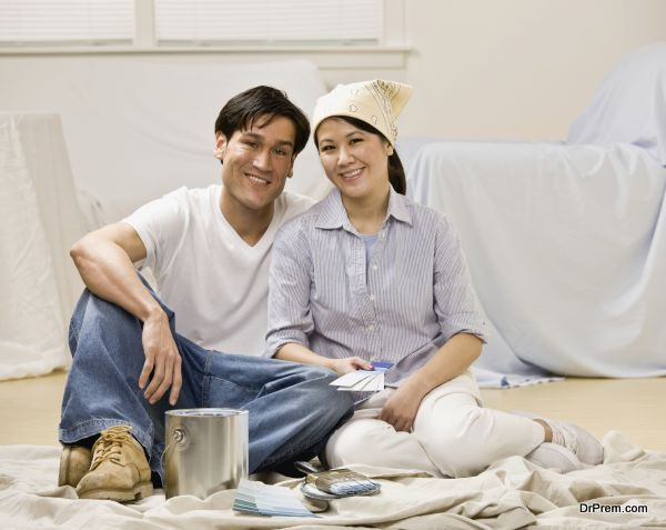 Couple sitting with paint can and paint swatch preparing to deco