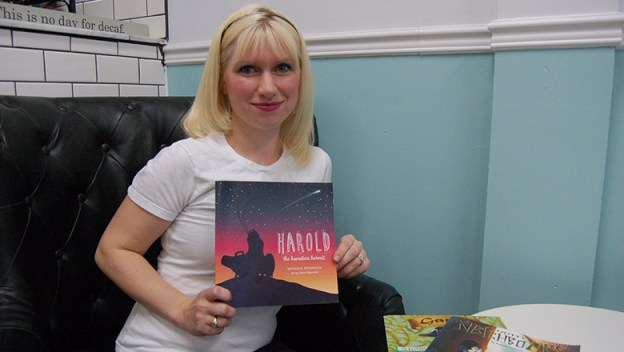 Natasha Peterson (author) holds up the children book she published.