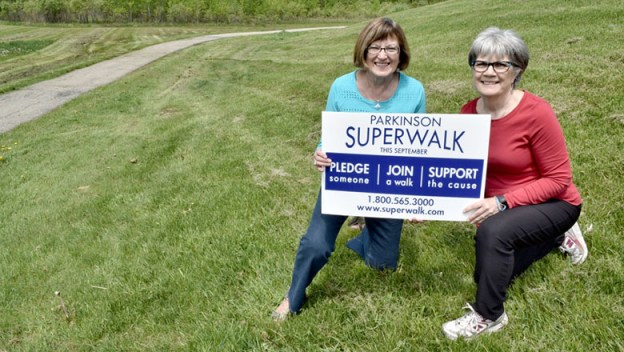 Ladies holding up a sign for SUPERWALK.