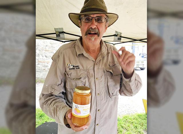 John Switzer holding a jar of honey.