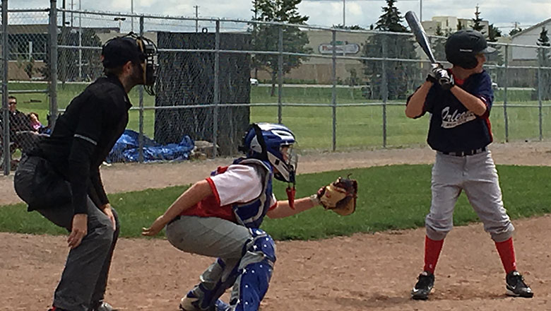 Umpire, back catcher and batter are waiting for the pitcher to pitch the ball.