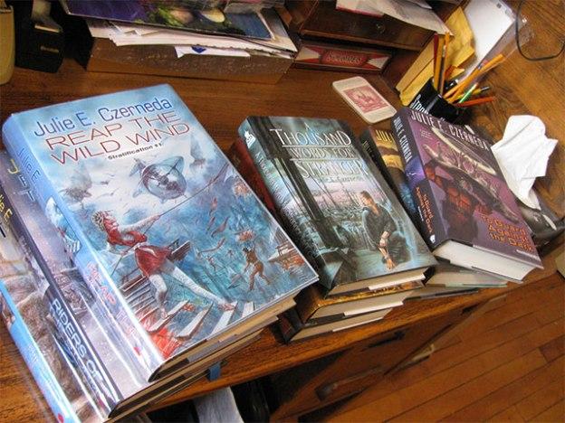 Julie Czarneda's books stacked on a shelf.