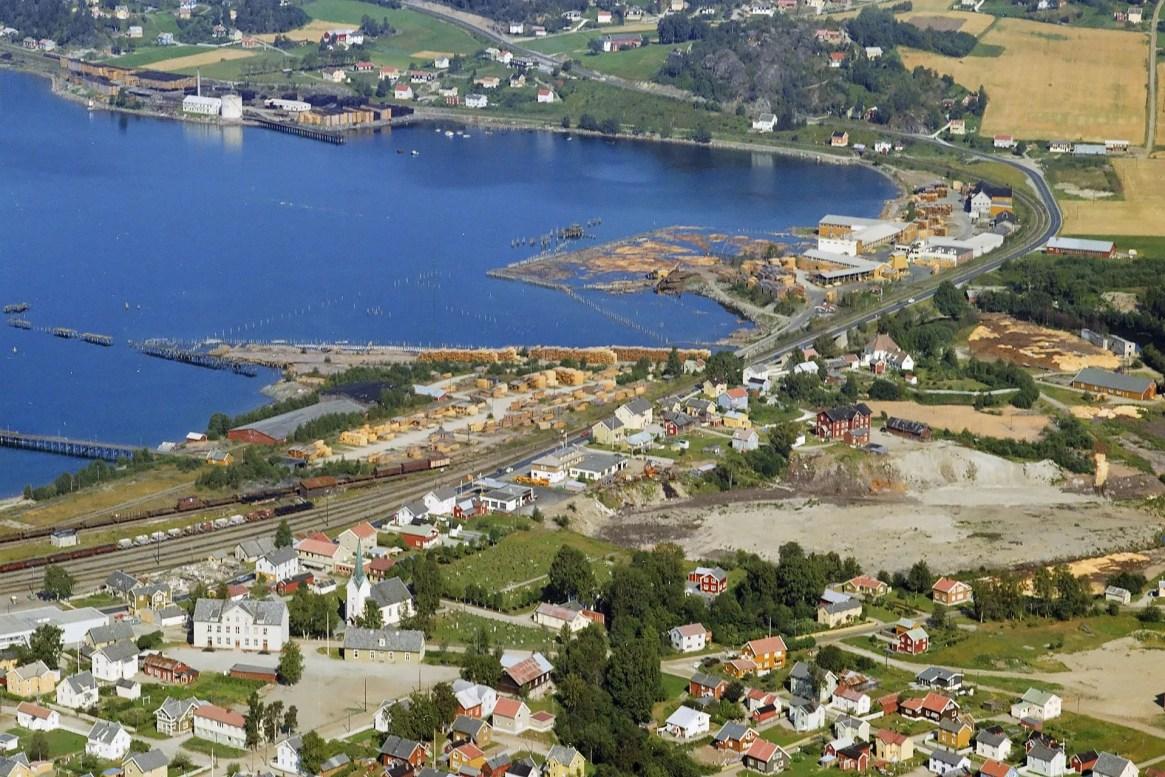 Hommelvik sentrum fotografert 16. august 1969 av Widerøe Flyfoto. Det som skal bli øya stadion ses i forgrunnen til høyre. Kilde: Nasjonalbiblioteket.