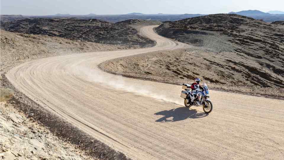 Honda Africa Twin Adventure Sports, trojštvrťový záber spredu z pravej strany, jazda po prašnej ceste v púšti