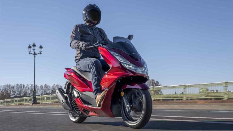 Honda PCX125 – trojštvrťový predný pohľad z pravej strany, zaparkovaný, jazdec stojaci vedľa sivého motocykla