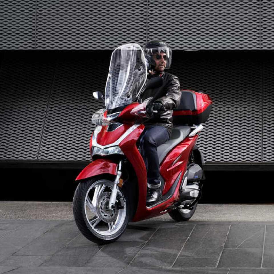 Honda-SH125i, trojštvrtinový pohľad spredu z ľavej strany s jazdcom pri parkovaní