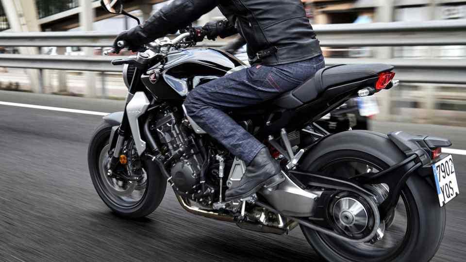 Trojštvrťový zadný pohľad na motocykel Honda New Sports Café CB1000R premávajúci sa po uliciach.
