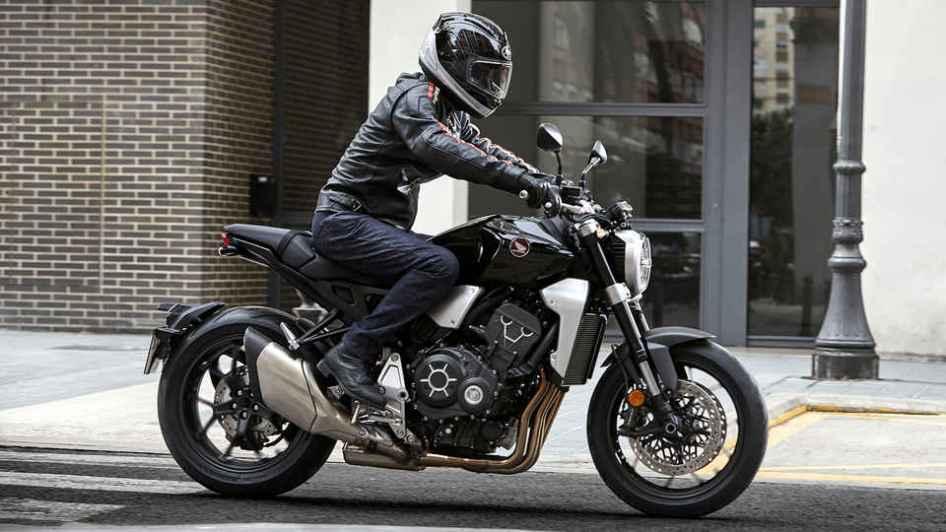 Bočný pohľad na jazdca sediaceho na motorke Honda Neo Sports Café CB1000R zaparkovanej pred budovou.