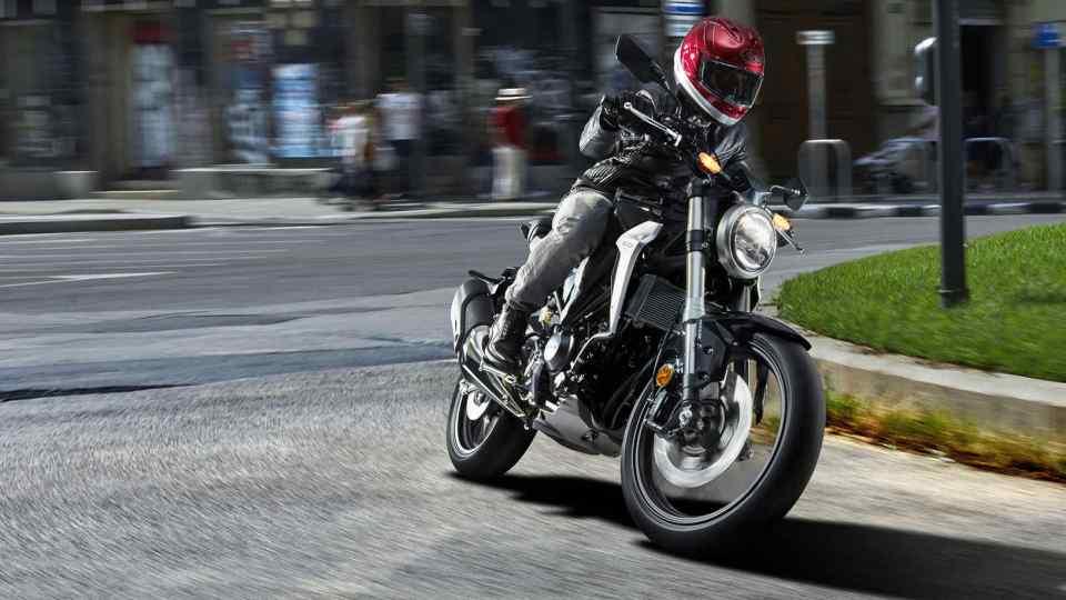 Predný trojštvrťový pohľad na motocykel Honda New Sports Café CB300R premávajúci sa po uliciach.