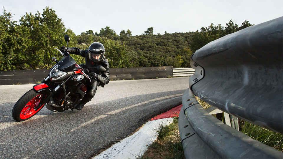 červeno-čierny motocykel NC750S pri jazde do zákruty