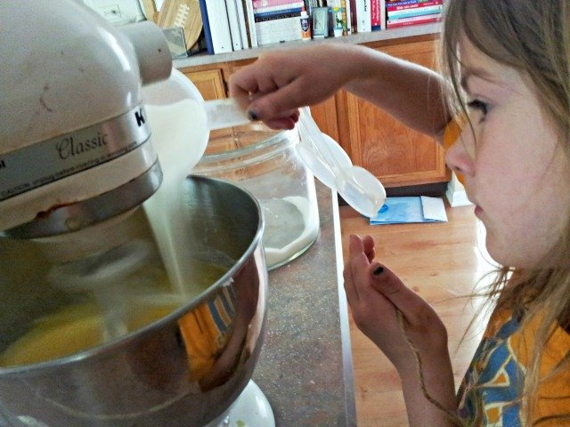 Little Miss adding the sugar while beating