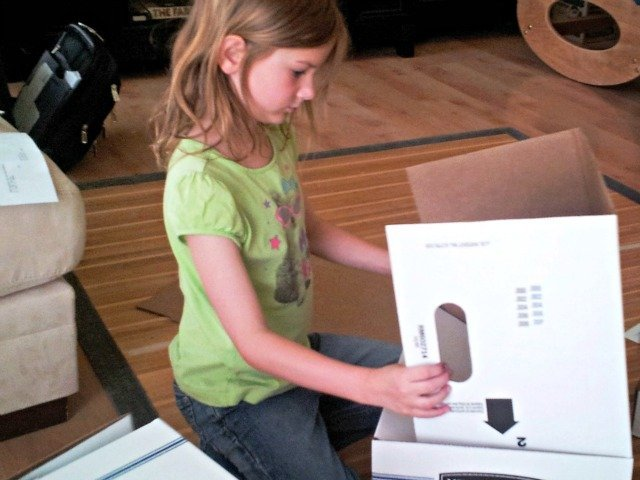 Little Miss turning the box around trying to figure it out
