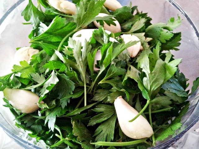 Herbs ready to chop for chimichurri almost fill the food processor bowl