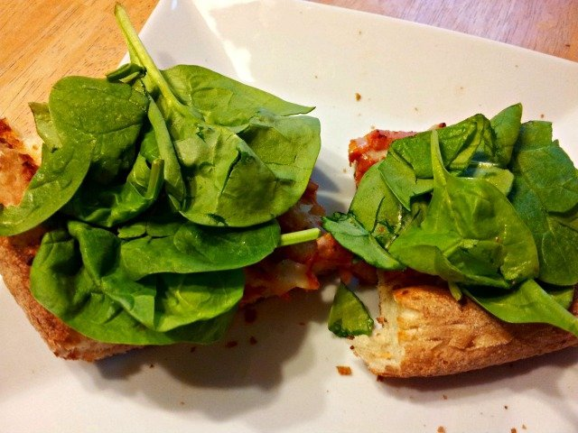 Add spinach to the top of pizza