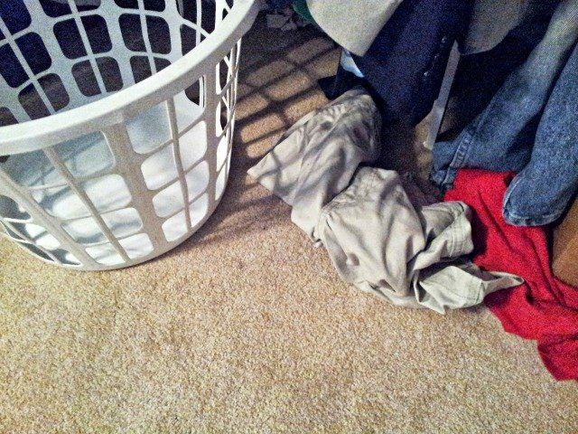 Laundry sitting all around but not in the basket