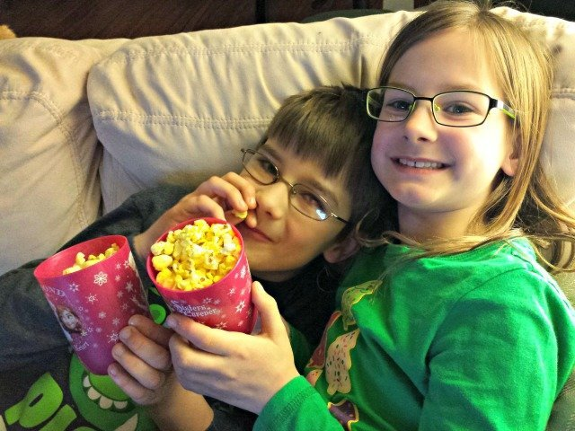 Wee ones snuggling on the couch and sharing popcorn