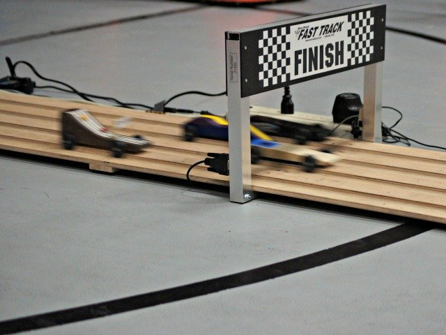 Racing Pinewood Derby cars on the track