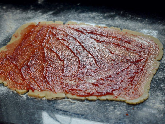 Spread cherry preserves over the dough rectangle