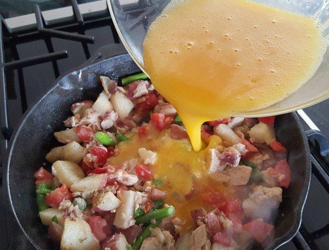 Pour beaten egg over nicoise dinner omelet mixture