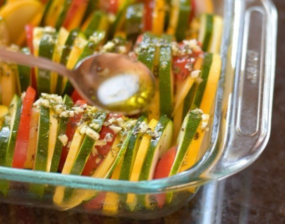 Drizzle olive oil and herbs over sliced veggies
