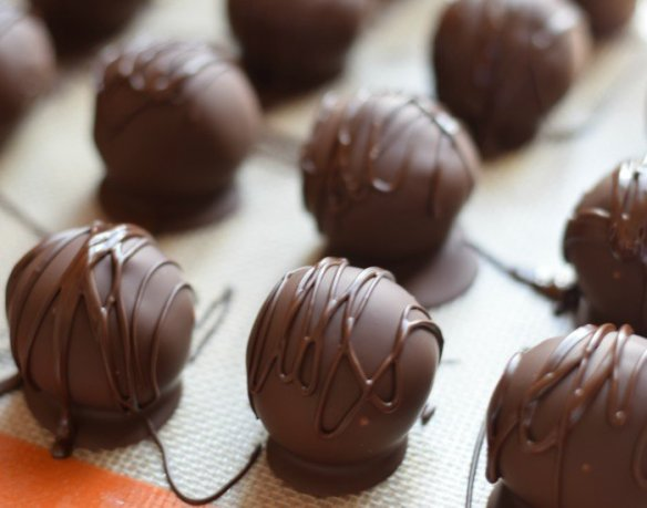 Use a fork to shake melted chocolate over hardened truffle shells