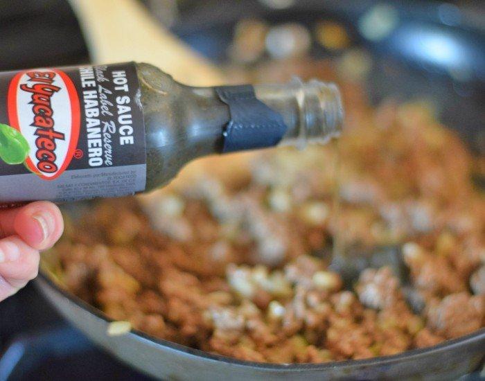 Add El Yucateco black label sauce to honey habanero beef empanadas