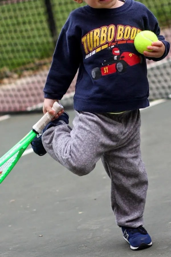 Little boy playing tennis with family