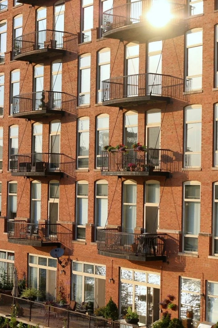 restored brick building with balconies overlooking river at sunset