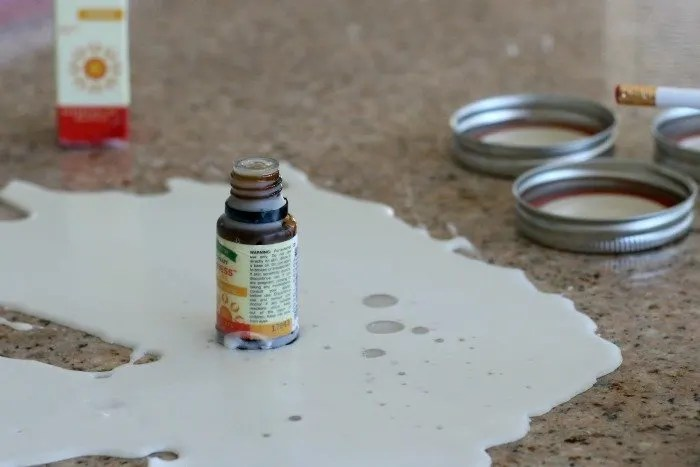 bottle of essential oil sitting in spilled wax