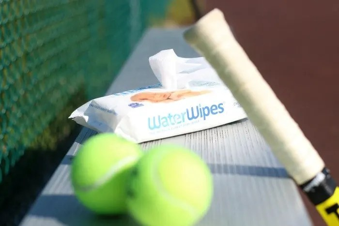 water wipes on a tennis court bench with a racquet and balls