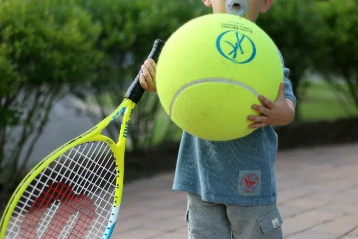 little boy holding oversize tennis ball and racket in burts bees kids clothes