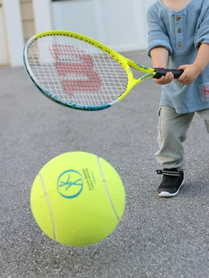 little boy playing tennis with oversize tennis ball and racket