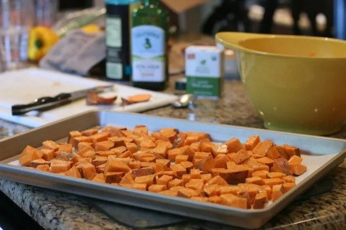 chopped sweet potatoes on a cookie sheet before being cooked