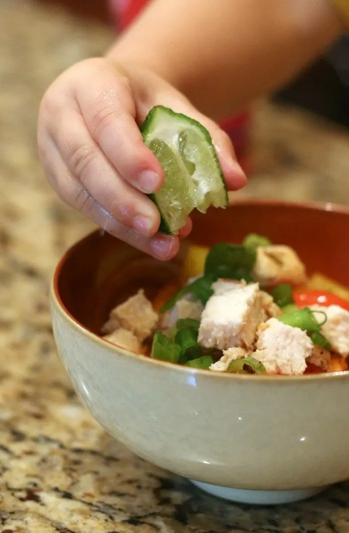little boy hand squeezing a lime onto a bowl of chicken and chopped vegetables