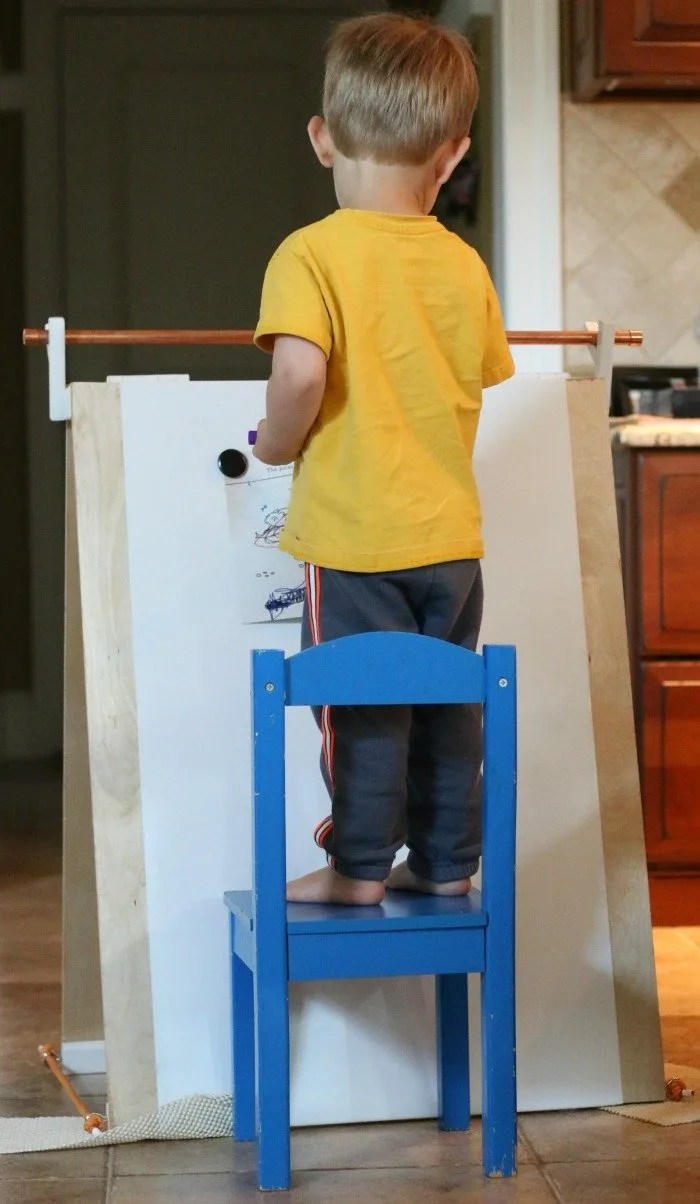 little-boy-standing-on-a-chair-and-coloring-on-a-handmade-easel